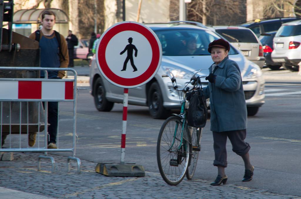 Paní přechází silnici  s kolem u zákazu vstupu chodců
